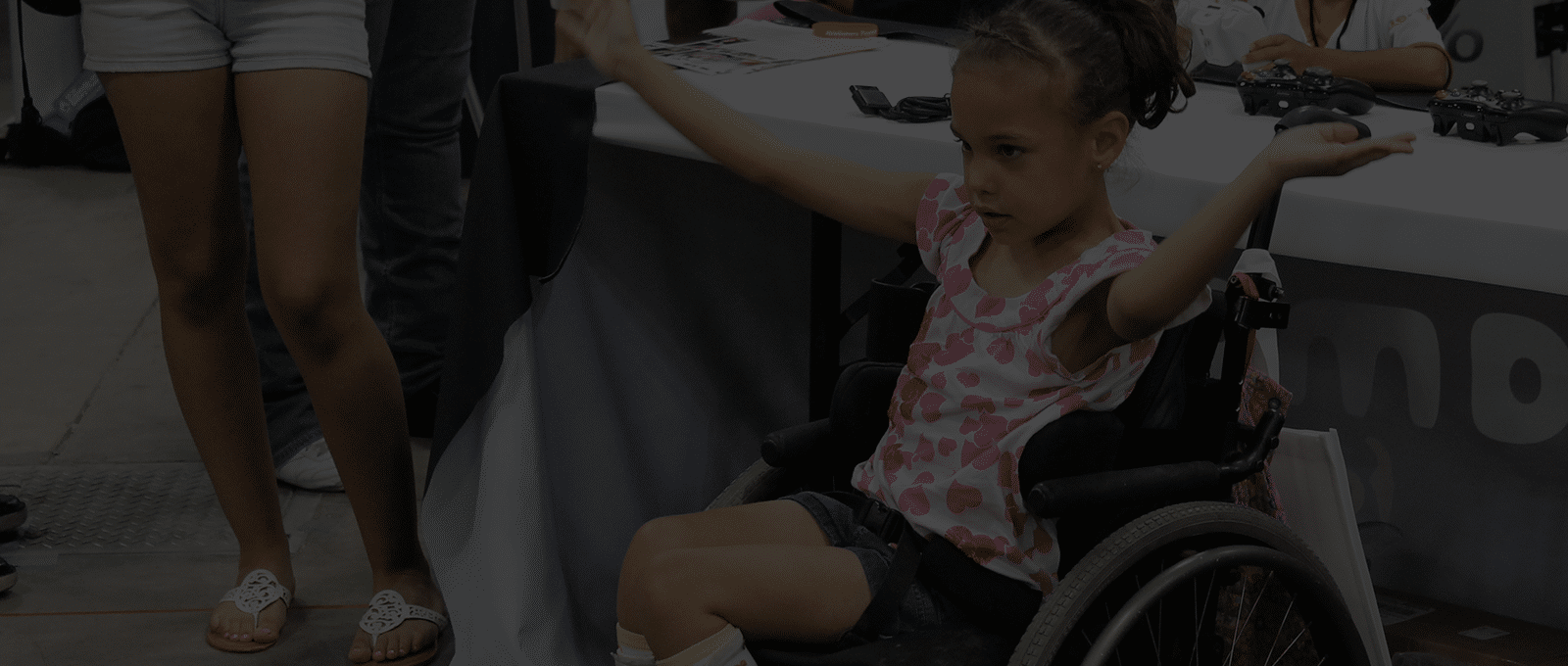 Photo of a little girl in a wheelchair playing Fruit Ninja