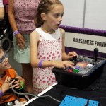 Two kids with disabilities play video games at an AbleGamers Booth