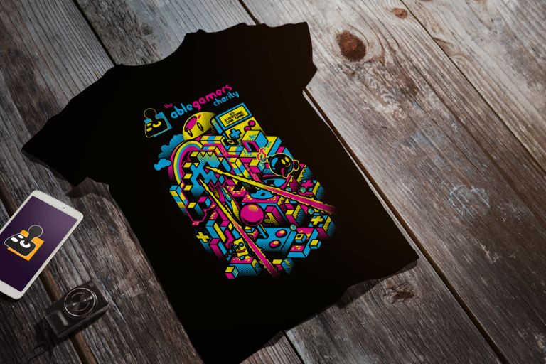 "A black tshirt with the multi-colored text ""The Ablegamers Charity"" in the top center. The central design includes a representation of 8-bit retro era game iconography."