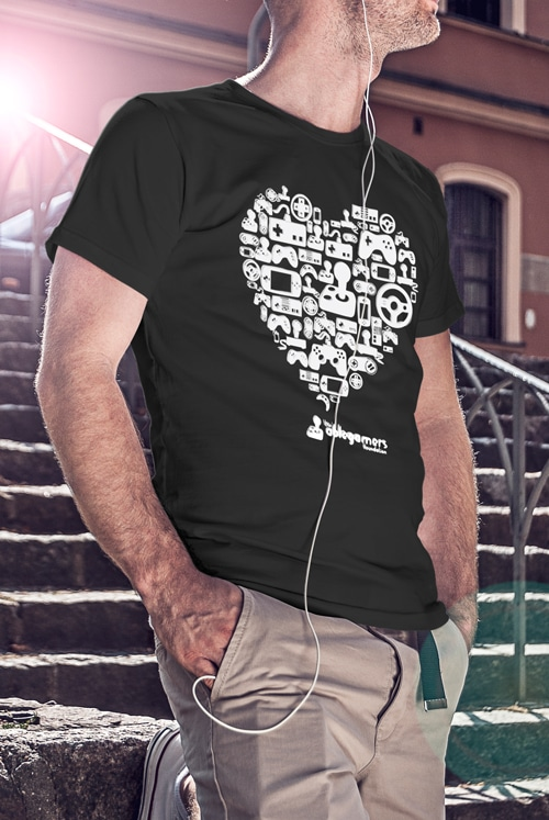 "A black tshirt with a large heart design in the center. The large heart design includes many different types of game controllers. The text ""The Ablegamers Foundation"" is located at the bottom of the heart."