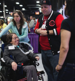 a girl in a wheelchair is helped by three volunteers to play video games