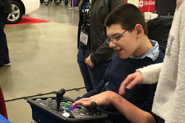 The disabled man in a wheelchair plays with an oversized joystick