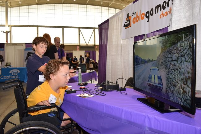 A small child, sitting in a wheelchair playing video games for the first time