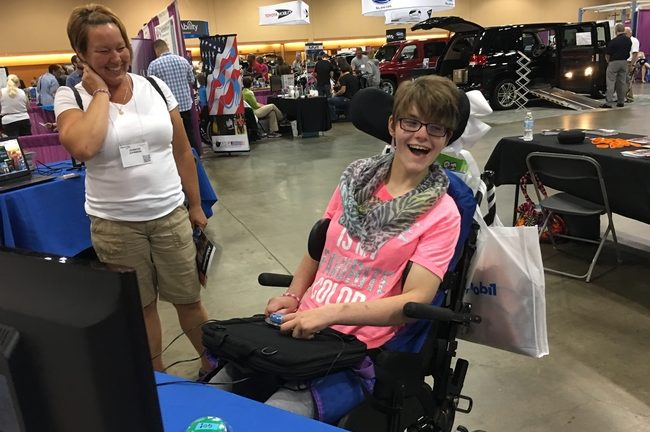 A woman in a pink shirt, sitting in a wheelchair smiles as she figures out how to play video games