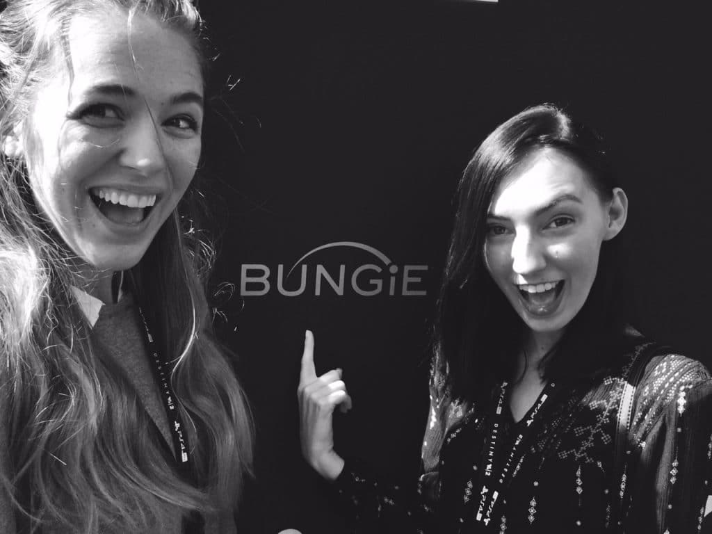 "Two women posing in front of the ""Bungie"" logo."