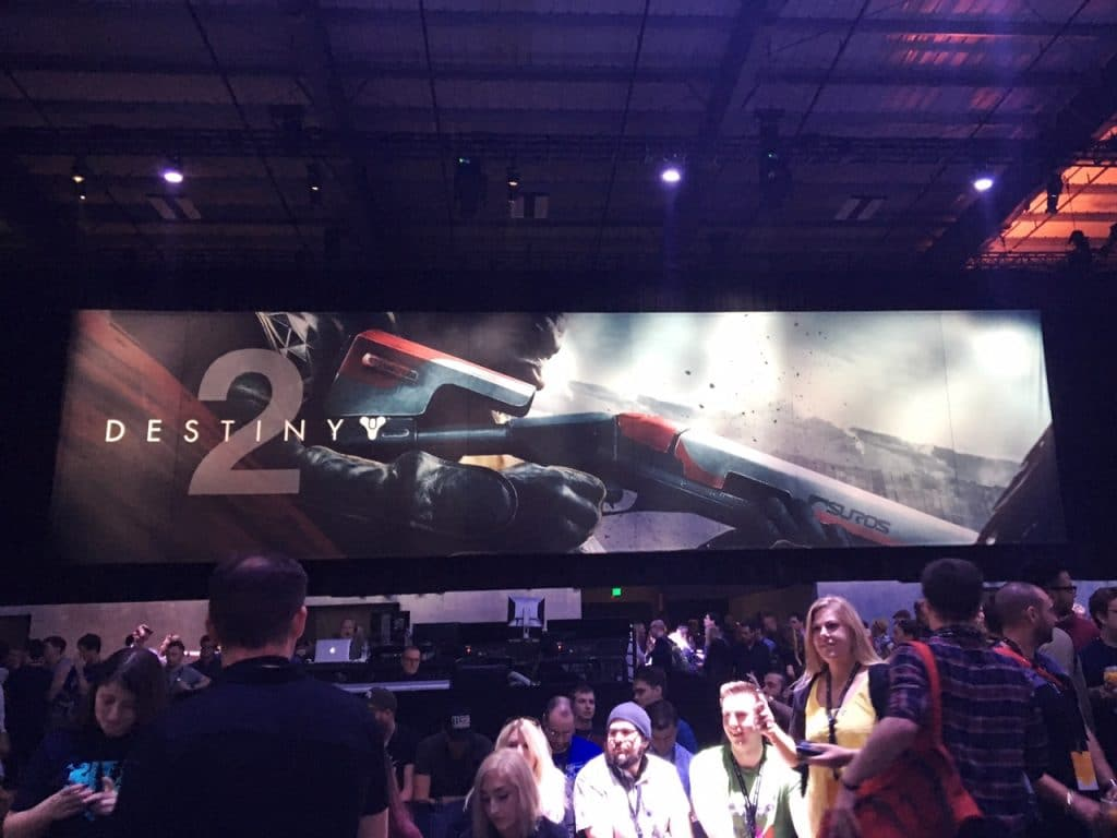 "Inside photo of Destiny 2 event, crowd of people standing in front of large banner that says ""Destiny 2"" on it with a man holding a shotgun branded with Suros."