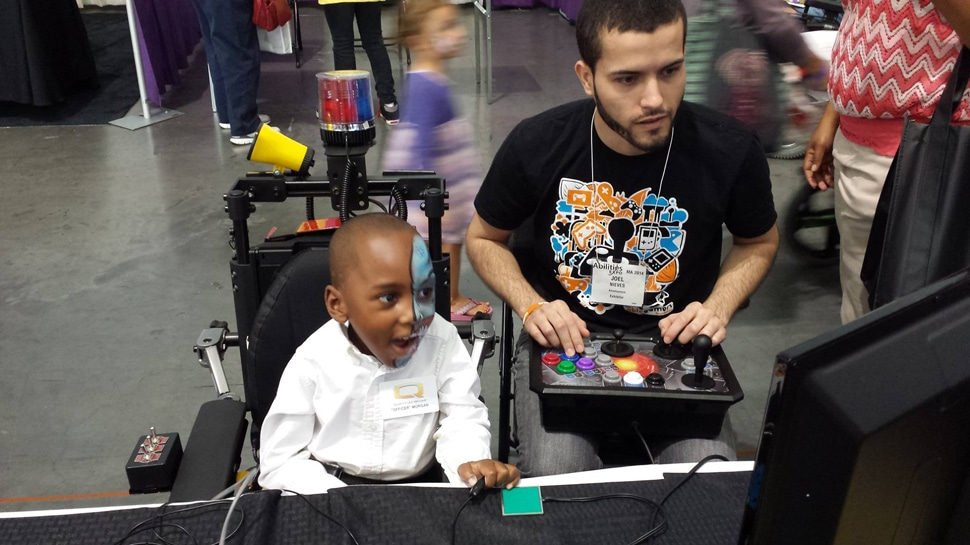 Joel playing games with a child both using accessible controllers