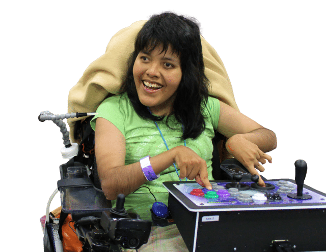A person in a wheelchair smiling while using the Axis 2 controller, an adaptive device with several large pushbuttons and three joysticks.