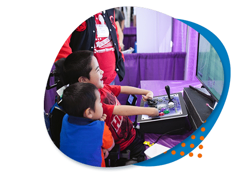 A royal blue roundish blob background small orange circles on top and on top of that a photo of a little boy laughing in a red t-shirt playing a video game using an adaptive controller while his little brother looks on