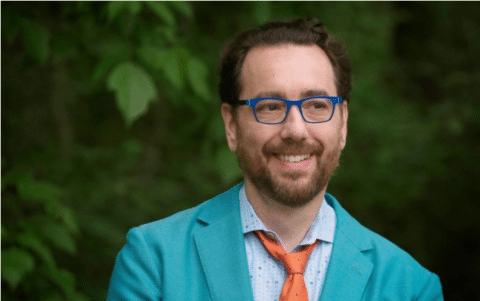 a smiling Mark Barlet, founder and Executive Director of the AbleGamers wearing a teal suit jacket, light blue shirt, orange tie and royal blue glasses