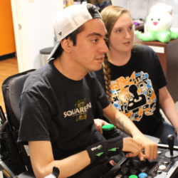 peer counselor helping a young man find the right adaptive controller