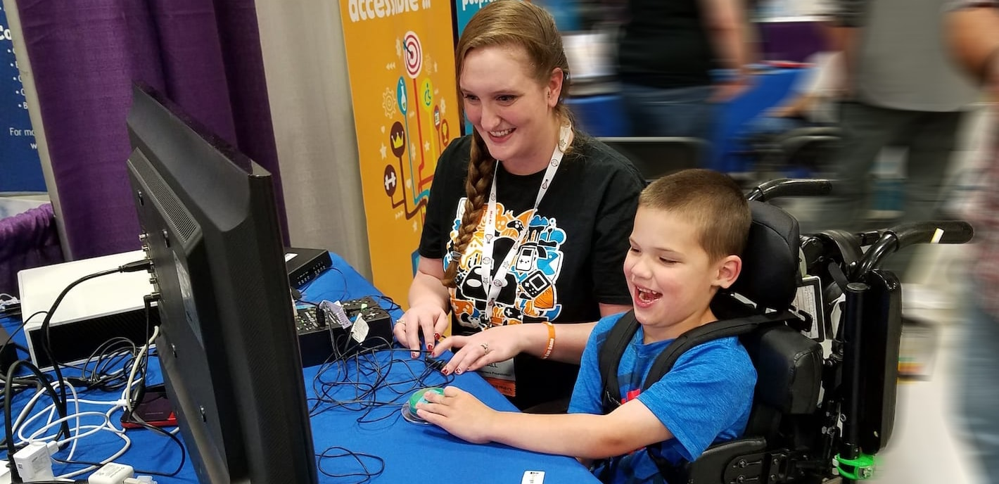 Peer Counselor playing video games with a young boy in a wheel chair