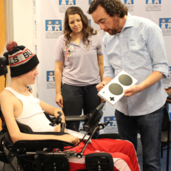 Mark Barlet showing a young man in a wheelchair an xbox adaptive controller while a young woman in a purple polo shirts looks on