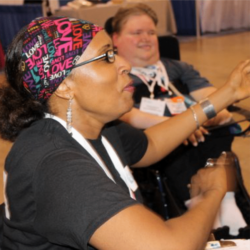 a woman having a lot of fun playing video games Steve Spohn is in the background watching