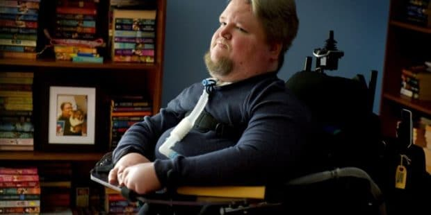 Steven Spohn, AbleGamers Chief Operating Officer sitting in front of a bookshelf full of books