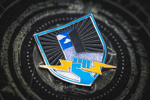 Everyone Can Play collectable pin is a shield with an open door to the sky in the background and a light blue fist holding a yellow lightning bolt in the foreground