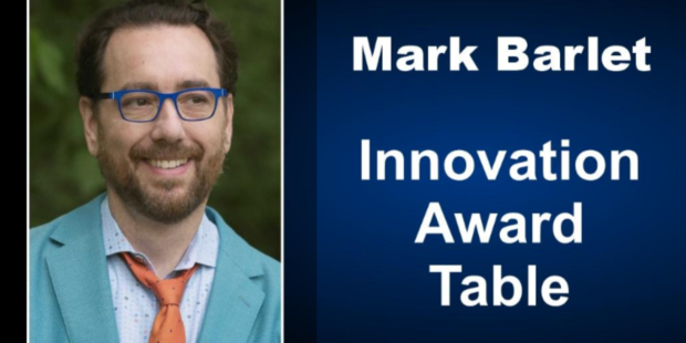 Mark Barlet head shot, he is wearing royal blue glasses, a teal suit jacket, blue dress shirt and AbleGamers orange tie. Next to Mark's photo is written Mark Barlet Innovation Award Table